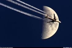 High over Boston, this 747-400 crosses a cold late afternoon Boston Winter moon