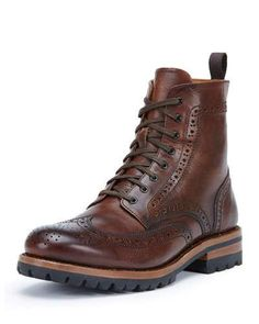 """Frye """"George"""" boot in Horween leather with brogue detailing. Approx. 6""""H shaft, 11"""" circ. Wing-tip toe. Lace-up front. Pull loop at back shaft. Leather lining and sole. Lugged rubber outsole. Goodyear"""
