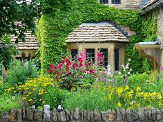 The oldest building in Greenfield Village was imported from England's Cotswold Hills to represent the area from which Henry Ford's ancestors immigrated. It is surrounded by a lush country garden.