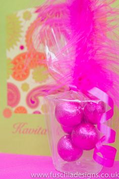 Best selling shotglass favour.  Great for Asian wedding favours as colourful and fun.  Metallic milk chocolate balls inside a plastic shot glass with matching coloured ribbons and feather.  Available in any colour of your choice from £1.99 each, other fillings available.  From www.fuschiadesigns.co.uk