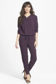A henley placket, chest patch pocket, drawstring ties at the waistline and zip cuffs style a long-sleeve jumpsuit crafted from featherweight threads.