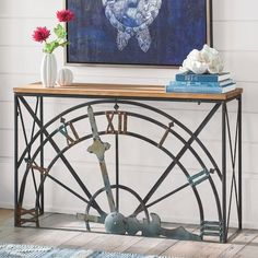 Time stands still only for the elegantly unique Tock Console. The frame of this playful but gracefully executed design features an elegant timepiece motif    on the front side, with the top portion of an oversized (non-working) clock. The antiqued, bronze-finish wrought iron frame is finished with a    rustic-style, fir wood top. A great idea as a serving station for cocktail hour, too.            Unique wrought iron and wood console table features a non-working vintage clock motif       ...