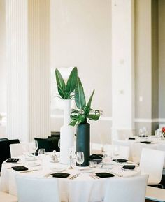 This black and white-themed, minimalist wedding opted for tall, matte black and white vases holding various types of greenery for a fresh, modern look