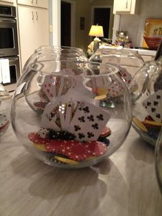 Casino party centerpieces made with fish bowls, playing cards, poker chips, and dice. Fish bowl decorations.