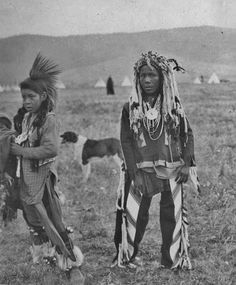 Flathead and Blackfeet boys pose outdoors wearing Native attire. A dog stands behind two of the boys. Teepees can be seen in the background. The Blackfeet boy may be of The Horn Society, wearing horned headdress. Native American Children, Native American Beauty, Native American Photos, Native American Tribes, Native American History, Native Americans, African Americans, American Women, Eskimo