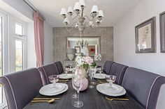 A luxury dining room with a sophisticated chandelier with envious table settings!