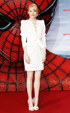 Emma Stone wearing an all-white Andrew Gn dress with dramatic shoulder-pads and Christian Louboutin shoes