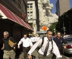 People run from the collapse of the World Trade Center on Fulton Street on Sept. 11, 2001. (Suzanne Plunkett/AP)