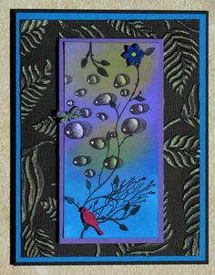 Designs by Ryn Water Droplets on blended distress inks.  Inkadinkado Meadow and Delicate Branches stamps.  CTMH wood embellies.Sizzix Peacocks and Leaves Set ef on Core'dinations Black Magic sanded paper.
