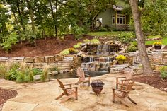 A two-tiered stone waterfall with a shallow pool sits just off the edge of a flagstone patio with a small fire pit. The flow of the waterfall follows the hill, with the home on the very top. Stone steps lead down from the backyard to the patio.