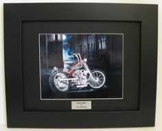 """Limited Edition Custom Framed Motorcycle Art Print, Indian Larry's Chain of Mystery Bobber, New York Cityscape, Signed & #'d w/COA - Original Painting by John Guillemette. The print is mounted in Raven black matting and set in Satin black wood framing. Centered at the bottom is a plaque with the title of the painting, """"Urban Legend"""", embossed in black lettering. The size is 11"""" x 14"""" (inside glass measurement). This artwork is signed and numbered by the artist and comes with a certificate…"""