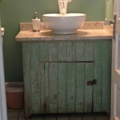 My office powder  room w old farm cabinet used as base for simple white bowl sink