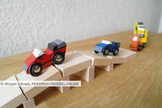 Brücke aus den Holzbausteinen der Spielgabe 6 nach Froebel mit Autos, die darüber fahren