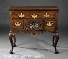 An American Chippendale Carved Mahogany Dressing Table, c. 1770, Philadelphia, stepped and molded top on case with inset fluted corner columns, a long drawer and three short drawers; the center drawer carved with shell and scrolling vines; having scalloped apron and return, cabriole legs with scrolling acanthus carved knees, claw and ball feet; brasses appear original, partially retains original surface, the top reset and conserved, height 31 3/4 in., width 34 in., depth 21 in.