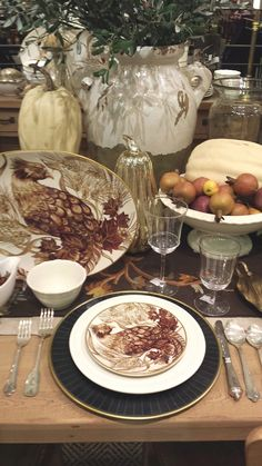 Thanksgiving Table with turkey plates and pumpkins and gourds in the center