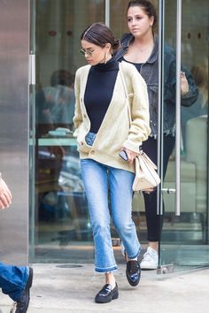 Selena Gomez looks cozy and cool in a chunky sweater, turtleneck sweater, crop jeans and loafer flats.