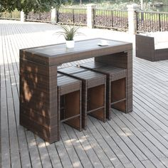 The Portfolio Aldrich set features a bar height table and 6 armless stools in dark brown resin wicker and composite wood. Ideal for small space living, this set can be used for both indoor and outdoor spaces.