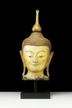 A gilt and lacquered teakwood head of Buddha Burma, Shan States, 18th/19th Century The face boyish and serene, with long earlobes and a conical usnisha rising to a lotus knop,  46cm.(18in.) high