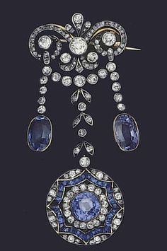 A belle époque sapphire and diamond brooch, circa 1900. The scrolling surmount of old brilliant and single-cut diamonds, suspending three graduating lines of single-cut diamonds, two terminating in an oval mixed-cut sapphire, the central one terminating in a circular pierced cluster decorated with circular and calibré-cut sapphires and single-cut diamonds, with fitted case.