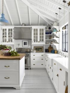 Bright peaked ceiling white and grey kitchen blue pendant white painted floors sink window