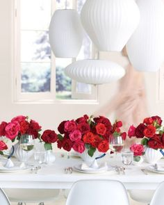 Rose Centerpiece  Table arrangements for your wedding in lush red hues. Create a twist on a classic by bundling blooms together in every shade of red -- from deep crimson to bright fuchsia -- and display them on an all-white tablescape.