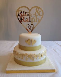 Golden wedding anniversary cake with mirrored acrylic name cake topper and real gold leaf covered hearts.