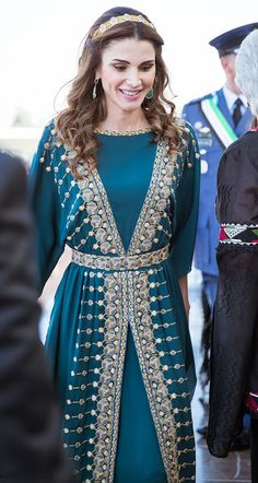 Queen Rania of Jordan opted for a more traditional-looking gown. The intricate outfit featured gold and blue detail across the front and the back, which the Queen complemented with pear-shaped green drop earrings.