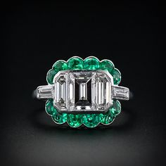 Diamond and emerald Art Deco ring, c. 1925. A fine one carat emerald-cut diamond flanked by two elongated half-moon shaped diamonds are set seamlessly across the top of this gorgeous ring for a scintillating effect. A surround of twelve deep crystal green calibre-cut emeralds and two baguette cut diamonds completes this spectacular platinum ring from the pinnacle of the Art Deco era.
