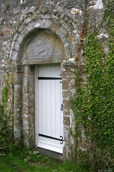 Penmon South doorway c 1150. Above the door is the carved figure of a Dragon with it's head twisted backwards