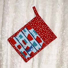 Handmade pot holder featuring a designer fabric of vibrant tableware and a coordinating red pattern to add fun to your kitchen. This pot holder