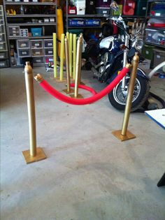 """Homemade theater stanchions. Used a 6"""" square of plywood on bottom. Screw in a wooden dowel to the plywood and cover with a pool noodle. Cut the top off of a 16oz pop bottle for the top of the stand. Use the bottom of the pop bottle to attach to the red pool noodle to make the rope and attach a cup hook to hook it to the stand. Use an eyelet screw on the stand to attach the """"rope""""."""