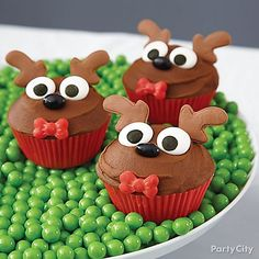 """Let your taste buds take flight with these Reindeer Cupcakes! Put them on display on a bed of """"grass"""" made of green gumballs or Sixlets®. Click for our how-to details!"""
