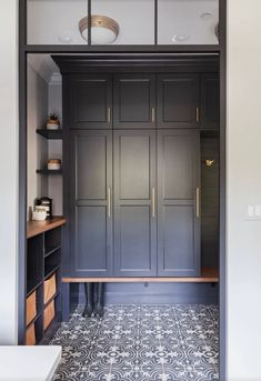 Black and white quatrefoil cement tiles charm a mudroom and laundry room combo showcasing black stacked cabinets with brass pulls. Mudroom Cabinets, Mudroom Laundry Room, Tall Cabinets, Built In Furniture, Studio Kitchen, Built In Wardrobe, Closet Built Ins, My New Room, Display Shelves