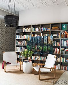 Add inviting seating in front of shelving to section off your library area. It also makes a large space look cozier.  Source: William Waldron via Elle Decor