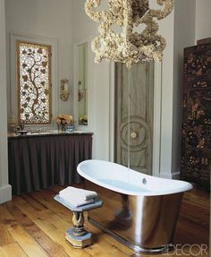 This master bath's tub-filler chandelier and laser-cut window panels are by Fisher Weisman; the tub and sink fittings are by Waterworks, and the Regency-style table is vintage.