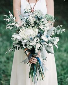 A loose bouquet of baby blue eucalyptus, white anemones, king protea, grey dusty miller, blue thistles, white heather, queen anne's lace, rosemary, and sage wrapped in hanging copper ribbons