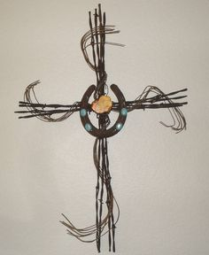 This is a cross I made. It features rusty barbed wire strands, wrapped with rusty baling wire, all salvaged material found here in Arizona.    It is accented at the center with a salvaged horseshoe that has been decorated with turquoise and orange natural stones - also native to Arizona. $39.95