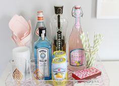 Editor @Alaina Marie Kaczmarski's Home Tour // bar cart // @Emily Mattie Luxe pink monogrammed lucite tray // stripe straws // @Design Darling matches // pink @Tracy Sferra cocktail napkins