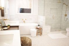A glass and brass shower enclosure is filled with marble tiles lined with a Kohler Rainhead with ...