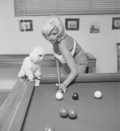 Jayne Mansfield plays pool in Rome with her poodle watching her every move.