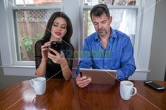 Office couple during meeting using a smartphones and a tablet at kitchen table during a morning coffee break | GoMobile Photography