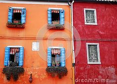 Photo taken on the island of Burano in the village of fishermen and lace embroiderers in the municipality of Venice Italy. In the image appear to be compared two bonded housing. The left one with the pink facade and open dark blue, to red right with dark ruined and closed.