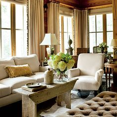 #tufted furniture: Linen curtains with vintage trim add elegance to this rustic living room.