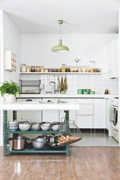 kitchen with industrial white cabinets on legs, green metal kitchen island large white square tile backsplash, floating shelves, wood floors.