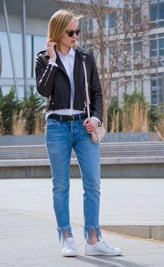 Street style look com calça jeans, jaqueta de couro e tênis.
