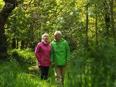 Older couple walking in forest together