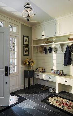Shiplap walls and charming built-ins add chic country style to this entryway mudroom.