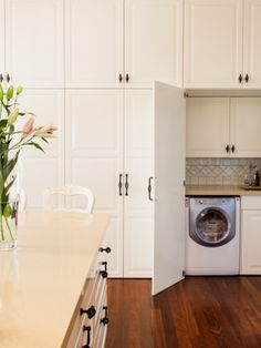 IKEA cabinets hide this European laundry.