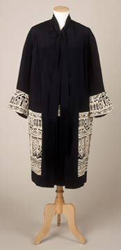 1925-30 Evening coat;  Evening coat of black ribbed rayon silk. Decorated around lower half, from low waistline to above hem, and around cuffs with deep band of white cotton machine embroidery. Two long ties of black rayon silk with long silk fringes at neckline. Unlined.  This coat has a matching evening dress of black rayon silk, decorated with the same white cotton machine embroidery.