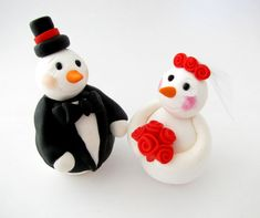 This is an adorable wedding or anniversary cake topper, featuring snowmen groom and bride . The perfect keepsake from your special day! The groom is wearing a black hat and a, a suit and a black bow tie. The bride is holding red flowers, wearing a veil and has red flowers on her head.